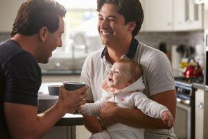 Male gay couple holding baby girl in their kitchen.
